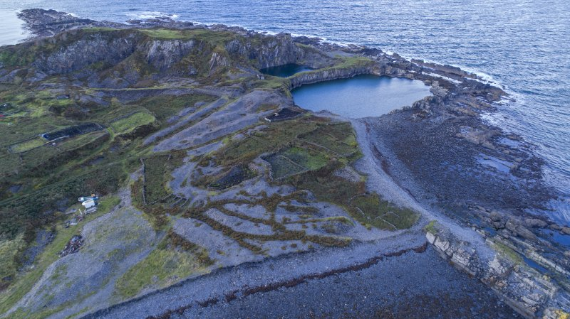 Oblique aerial view of west end of island showing Windmill Quarry, north spoil, walls and workings  and the eroded slate waste tipping which have truncated enclosure walls and tipping runs from quarrying activity