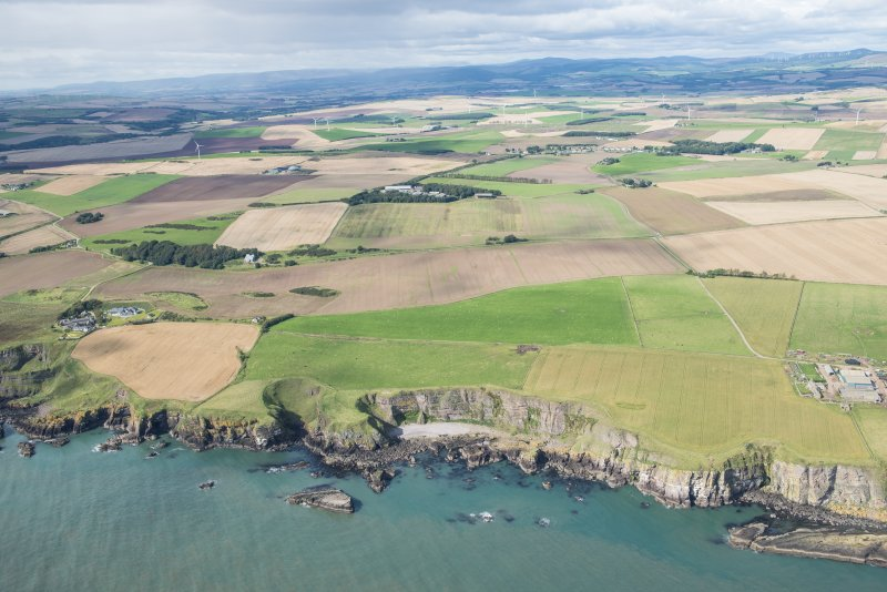 General oblique aerial view of the Aberdeenshire landscape centred on Adam's Castle and Roadside of Kinneff.