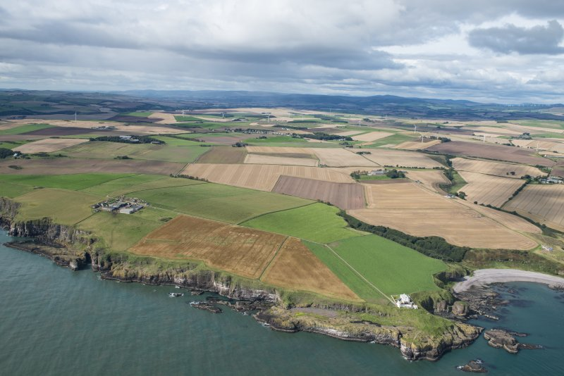 General oblique aerial view of the Aberdeenshire landscape centred on Todhead Lighthouse and Roadside of Kinneff.