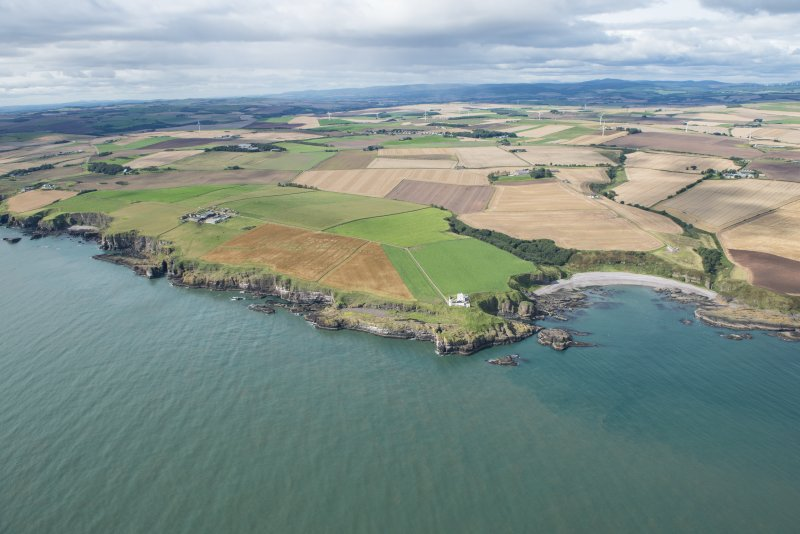 General oblique aerial view of the Aberdeenshire landscape centred on Braidon Bay, Todhead Lighthouse and Roadside of Kinneff.