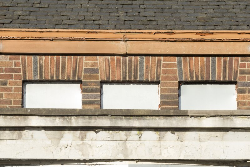 Detail of coloured brick pattern on clearstory level above loggia.