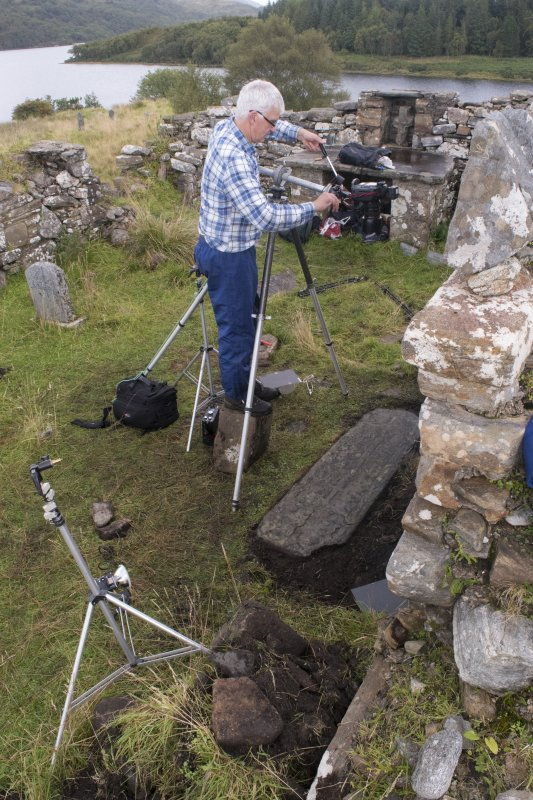Church interior. HES Photographer Steve Wallace recording the late medieval graveslab