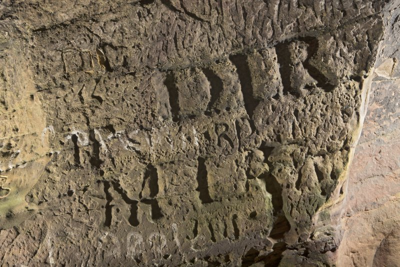 Detail of carved lettering on south wall of cave