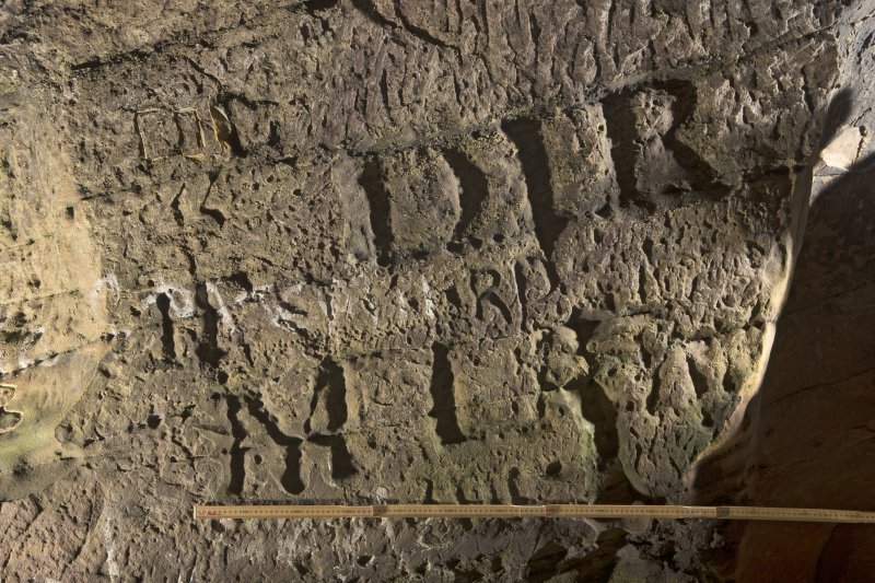 Detail of carved lettering on south wall of cave (including scale)