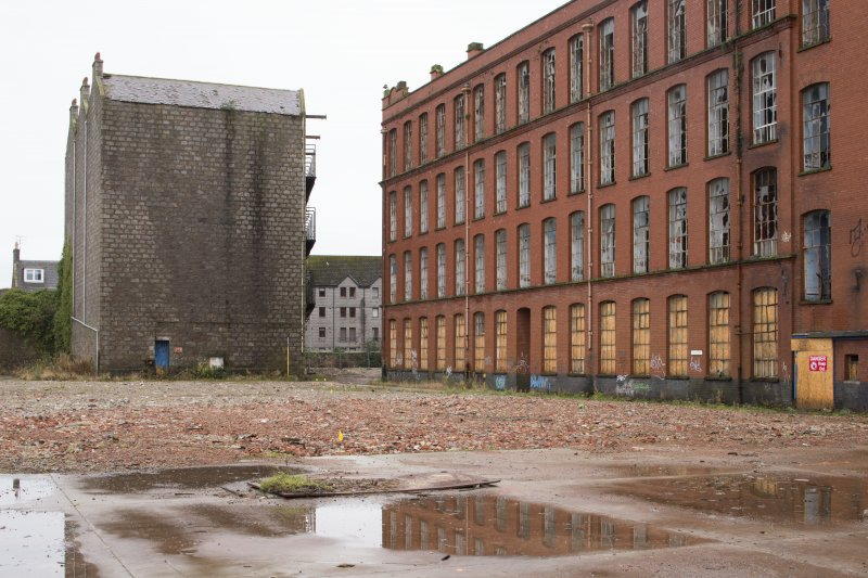 View from north of former jute warehouse (left) and New North and South Mills (1914). The small yellow flags show the line of the lade (culverted as the site was extended to the east).