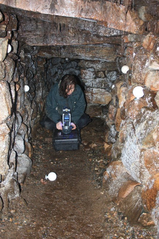 Archaeologist Gemma Hudson preparing equipment for the laser scan survey inside Cracknie souterrain, Tongue