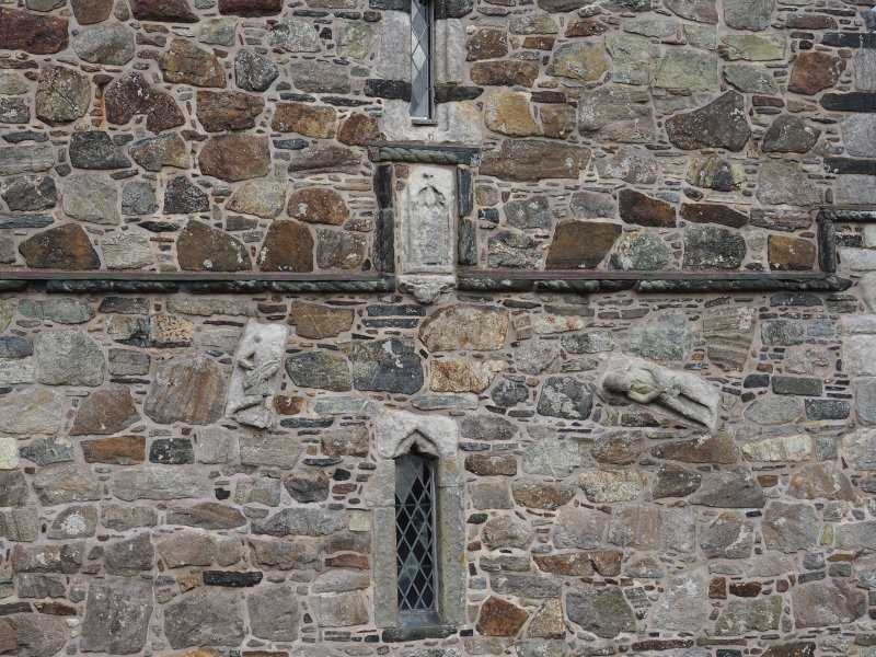 Rodel church. Exterior. Detail of three medieval carved stones incorporated in the E wall of the tower.