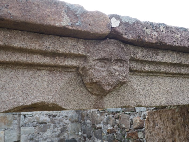 Rodel churchyard. Detail of carved head above entrance to burial enclosure.