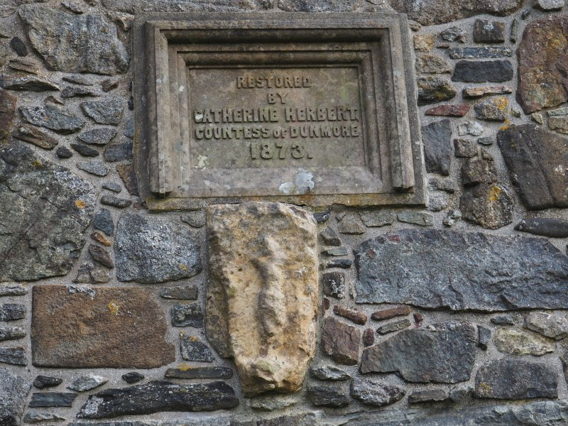 Rodel church. Exterior. Plaque commemorating the restoration of the church by Catherine Herbert, Countess of Dunmore, in 1873. Below this, an architectural fragment of medieval date showing a crucifixtion scene.