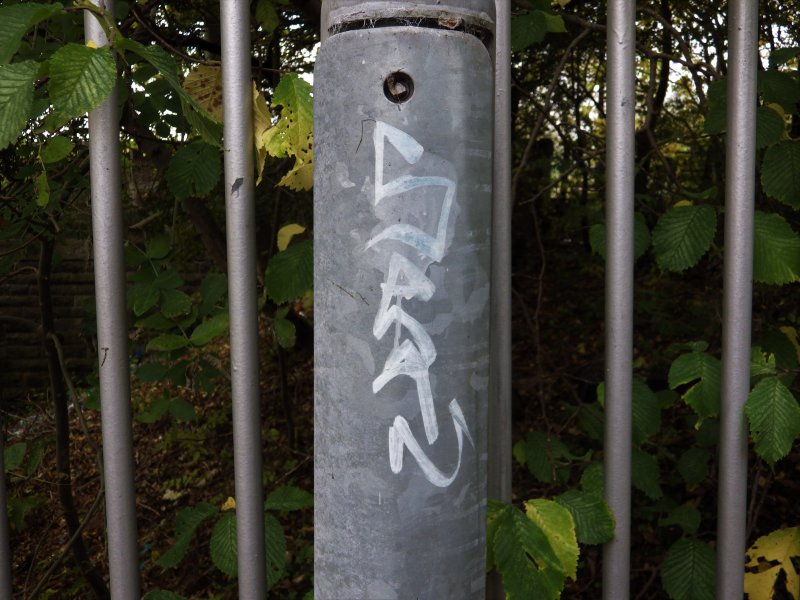 View of graffiti on a lamp-post on the footbridge.