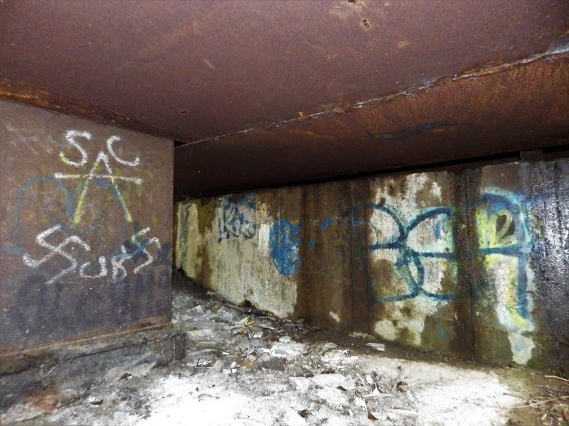 Image illustrating the poor condition of the graffiti written on the damp surfaces underneath the bridge.