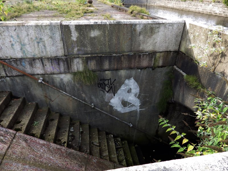 Graffiti on top edge of one of the stairways leading down into graving dock number 3 from its south side.