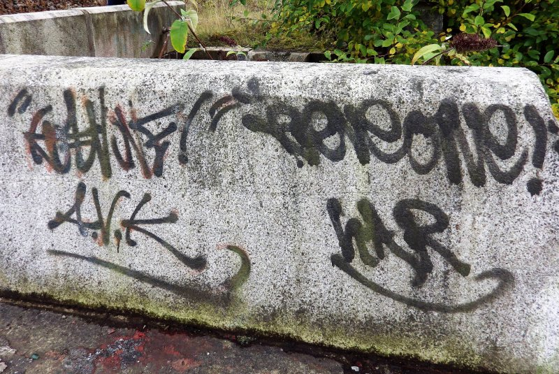 Graffiti on concrete block on top edge of one of the stairways leading down into graving dock number 3 from its south side.