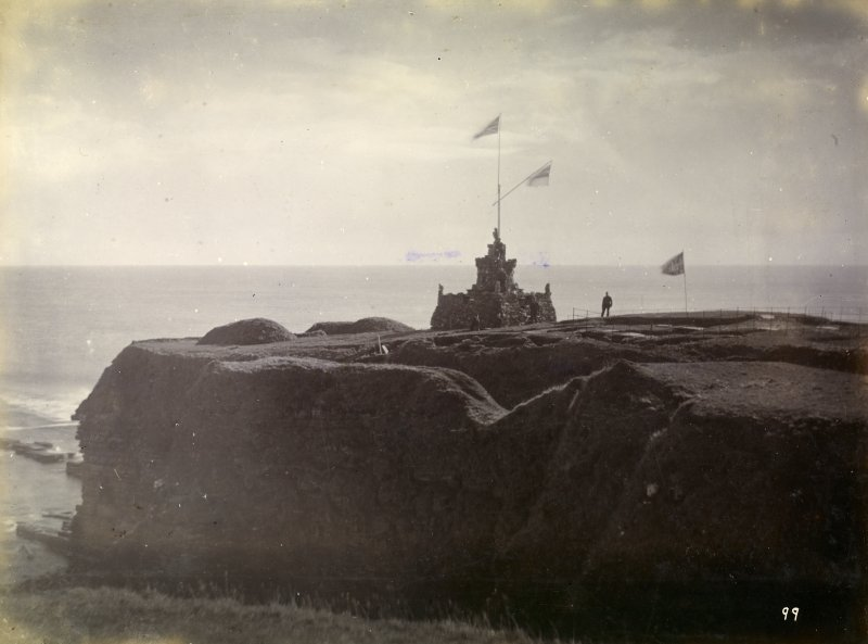 Photograph of Mervyn Tower at Nybster Broch on second promontory, shown with flags.