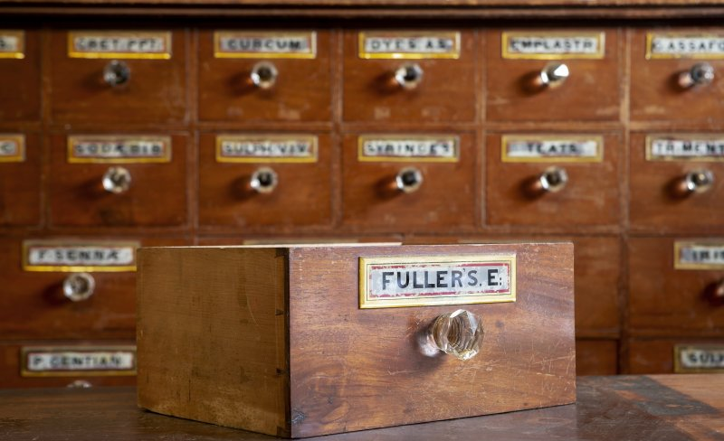 Coldstream, 81 High Street. Interior. Pharmacists medicine drawer. Detail showing 'FULLERS E.[arth]' drawer label (painted and gilded glass).