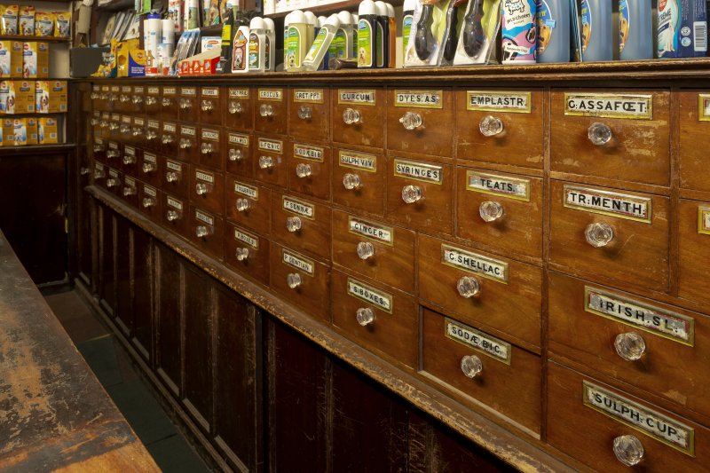 Coldstream, 81 High Street. Interior. Detail of bank of drawers with their glass painted and gilded labels and glass handles.
