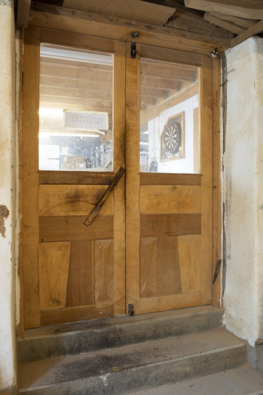 Interior view showing detail of door, including weighted closure system, in stables workshop at The Steading, Nether Blainslie.