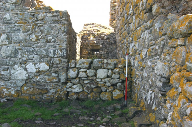 Historic building survey, McVicar Chapel, exterior, W-facing gable wall and blocking work adjacent to the Church wall, Teampull na Trionaid, Cairinis, North Uist, Western Isles