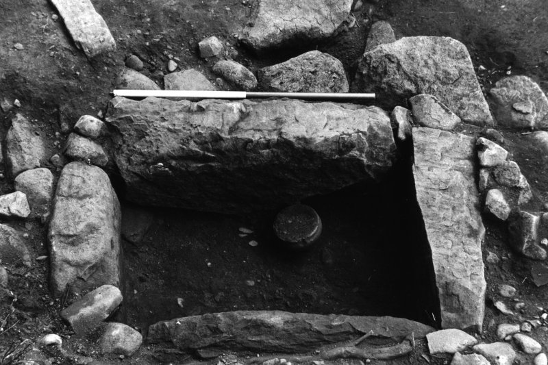 Excavation photograph showing cist with food vessel and knife.
