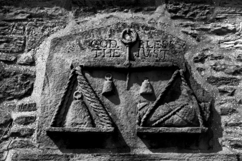 Detail of carved panel above south doorway showing weighing balance and inscribed 'God bless the just'