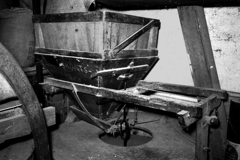 Machrimore Mill, interior. View of grain hopper and feed trough above groating stone showing cam and spring ('damsel') mechanism.