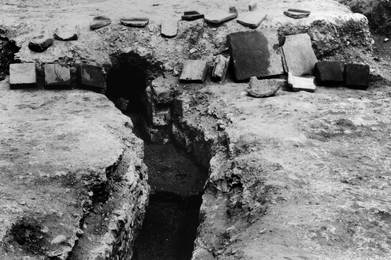 Excavation photograph: the residence flue no. 3, with step and division, looking N. The tiles were found in the ruins.