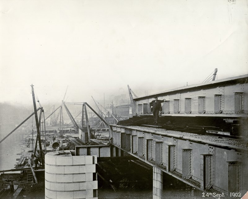 View from Clyde Place, Glasgow of the Central Station Bridge during construction, September 1902 (completed 1905). This was built for the Caledonian Railway Company to their design as part of the reconstruction of the Station. An earlier bridge built also by Arrol (1875-8) for the Caledonian Railway is just visible in the centre background. Its girders and decking had to be jacked up by 3 feet in order to achieve the rail level of the new bridge