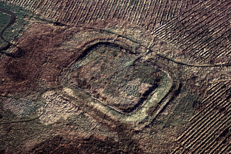 Oblique aerial view of Castle Greg Roman fortlet.  Ploughing for afforestation has encroahed right up to the earthworks.
