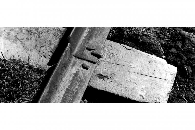 Detail of L-section rail affixed to wooden sleepers with spikes on mineral railway.