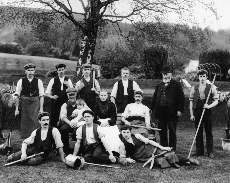 Gardeners at 'The Glen' Country House near Innerleithen, seated and standing in gardens, holding watering cans, shears, rakes and other gardening implements.