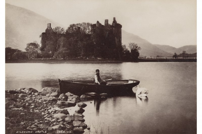 "Photograph showing general view of Kilchurn Castle, with man in boat in foreground, with swan beside boat Insc. ""Kilchurn Castle.  7962  J.V."""