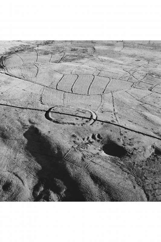 Oblique aerial view of Kirk Hill centred on the remains of a fort and palisaded enclosure with buildings, enclosures, lazy-beds, quarries and a farmstead, field-system, rig and boundary bank adjacent, taken from the WNW.
