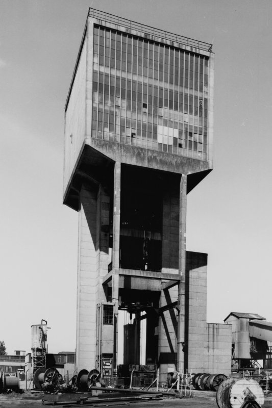 General view from S of no. 1 shaft winding tower, Monktonhall Colliery, built from re-inforced concrete, used to wind coal and men using two tower-mounted, geared, multi-rope A.C. friction winders with skip and counterweight, both manually controlled and equipped with dynamic braking.  No. 1 shaft is also the upcast air shaft.
