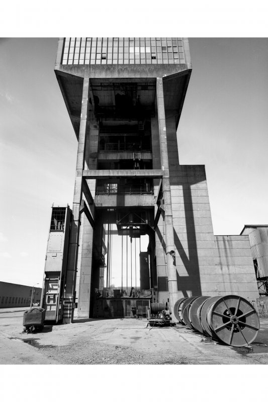 General view from S of No. 1 shaft winding tower, used to wind coal and men using two tower-mounted, geared, multi-rope A.C. friction winders with skip and counterweight, both manually controlled and equipped with dynamic breaking.  A spare skip can be seen to the left of the tower.
