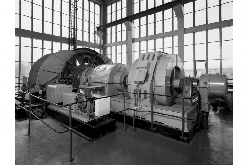 General view on top floor of no. 2 shaft tower showing the exciter from right to left, electric motor, gearbox and cable drum of the no. 2 winder.  This winder is equipped with one large cage and a counterweight on wood guides, and can carry 130 men on two decks.