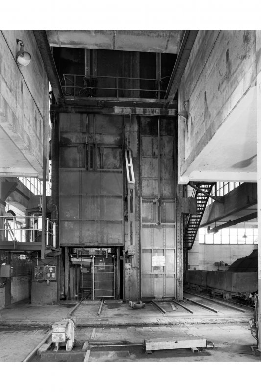 General view of car hall at top of No. 2 shaft, showing cage with door open, and vertical sliding door in raised position.  The protective steel doors and walls around the top of the shaft are designed to seal the shaft, protecting the flow of downcast air from the adjacent fan house into the mine.  Monktonhall Colliery.