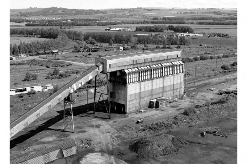 General view from top of No. 1 shaft winding-tower (from West) of the 3180 tonne rapid-loading surface bunker, capable of loading five 32-tonne wagons simultaneously, loading a complete 29-wagon train in about 30 minutes.  When working, trains delivered all the mine's daily output of coal to Cockenzie Power Station nearby.