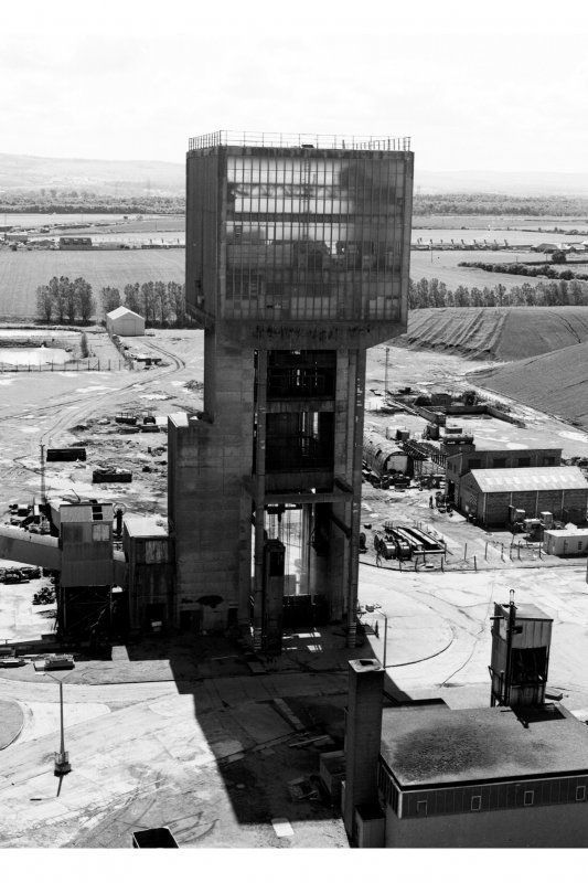 View from N of No. 2 winding tower of No. 1 winding tower, used to wind coal and men using two tower-mounted, geared, multirope A.C. friction winders with skip and counterweight, both manually controlled and equipped with dynamic braking.  The boilerhouse can also be seen (bottom right).