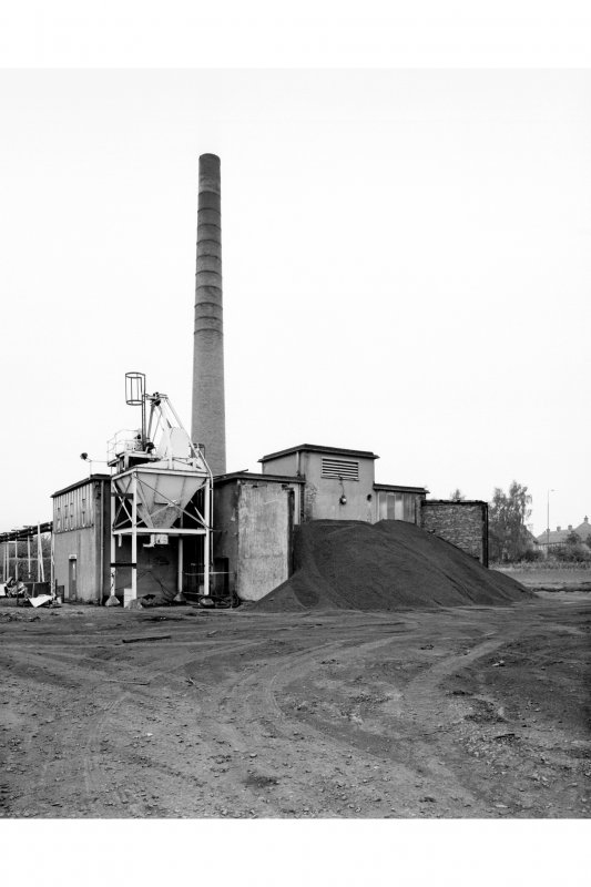 General view from SE of boilerhouse, coal hopper (obscured by coal stock), ash hopper, and chimney stalk.