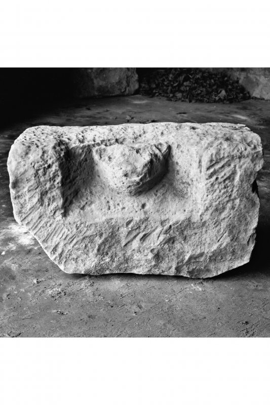View of dressed sandstone block with coped sides and bearing a cat like head in high relief, held in the garage behind the manse.