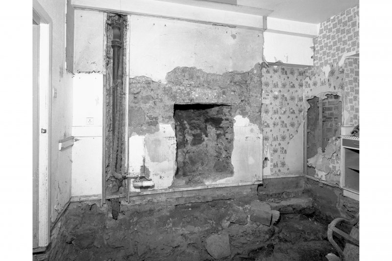 View from North West showing original floor level and exposed fireplace, room 9