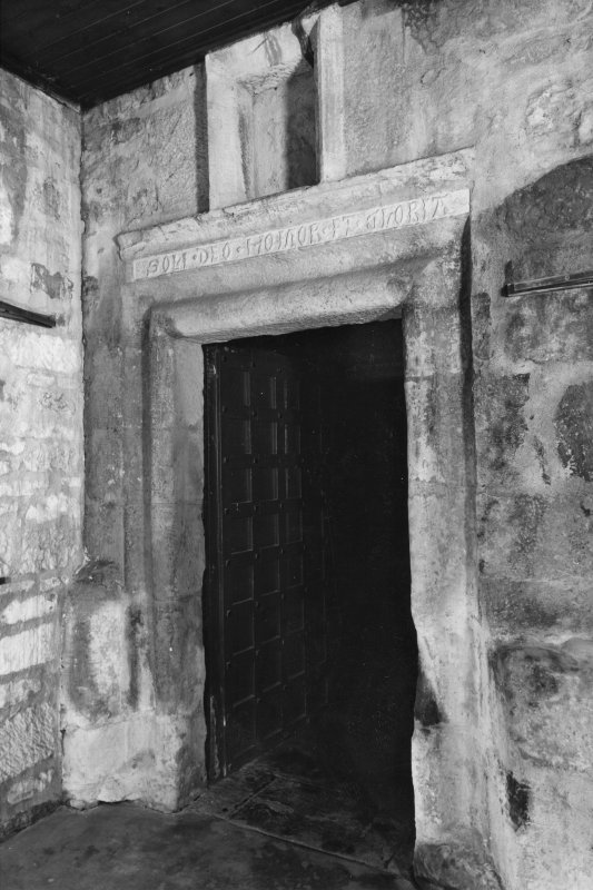 Interior. Tower, detail of moulded stone doorpiece with inscribed lintel.