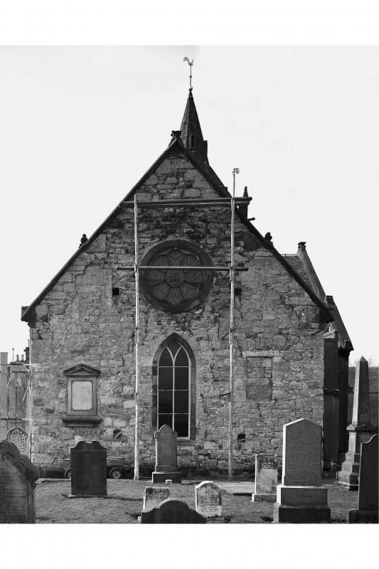 View of East gable with scaffolding and gravestones.