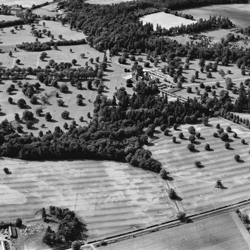 Mains of Glamis and Glamis Castle, oblique aerial view, taken from the E, showing a pair of linear cropmarks in the bottom half of the photograph, and further cropmarks in the bottom right-hand corner. Glamis Castle is visible in the centre.