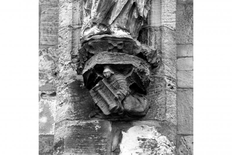Detail showing a corbel with a carved angel holding 'arma Christi' emblem; South front, South range