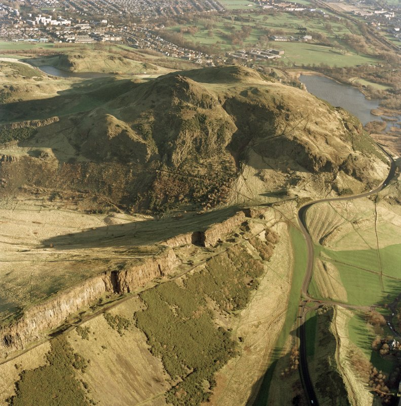 Oblique aerial view of Holyrood Park centred on the remains of quarries on Salisbury Crags with Arthur's Seat behind, taken from the WSW.