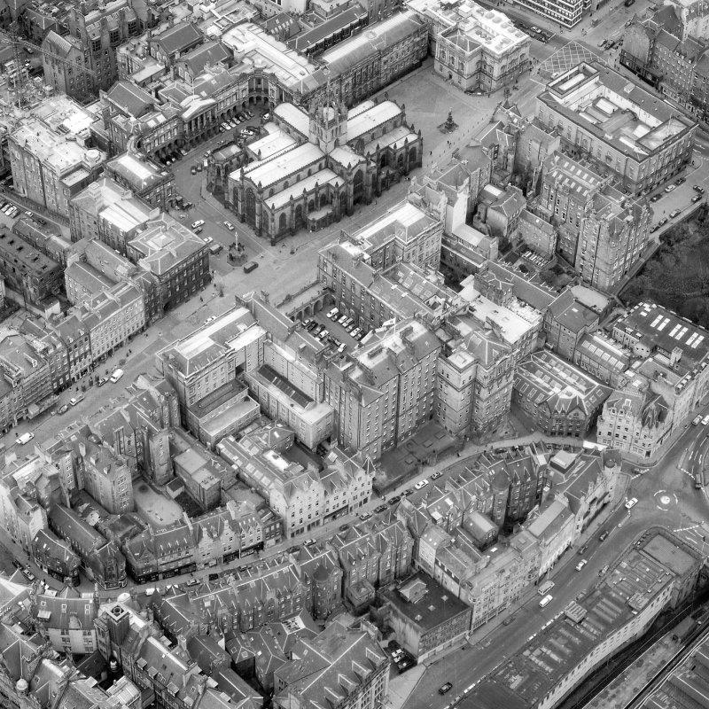 Oblique aerial view showing High Street between North Bridge and Lawnmarket with Cockburn Street at bottom of photo, City Chambers in centre and St Giles' Cathedral at top