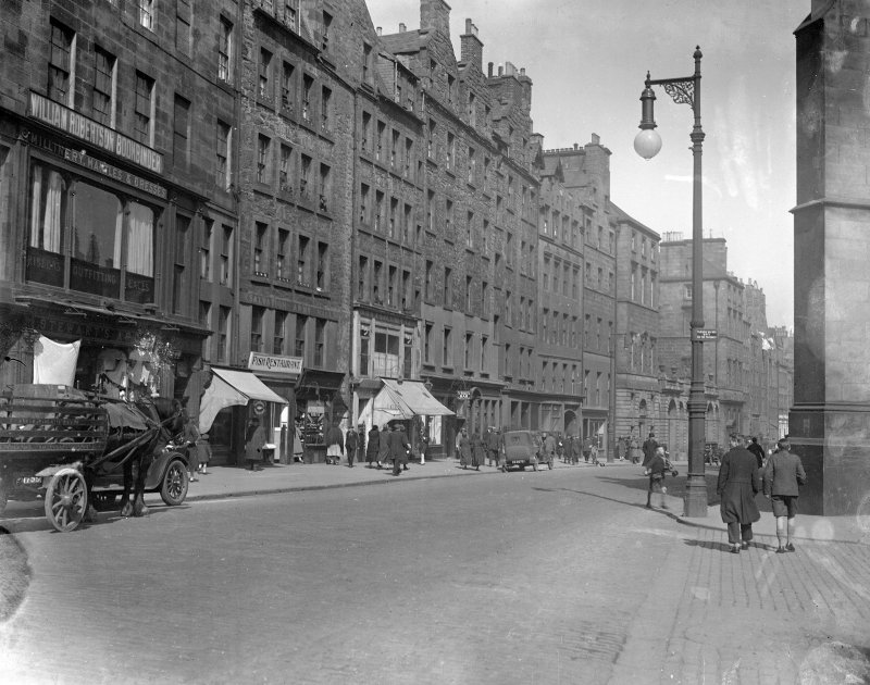 General view of the High Street, Edinburgh, before extension to City Chambers showing a clothes shop, a fish restaurant, the Venetian Cafe, and St Giles Bar