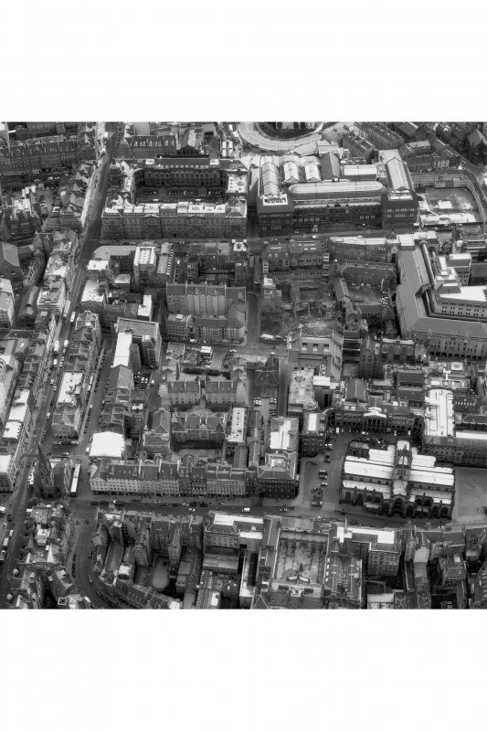 Oblique aerial view of centre of Edinburgh including South Bridge to left of photograph, Old College and Royal Museum of Scotland at top, Parliament Square, High Court to right and City Chambers at bottom
