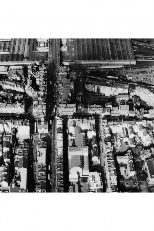 Oblique aerial view of centre of Edinburgh including High Street running left to right across centre of photograph and North and South Bridges running top to bottom